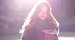 Young brunette woman with long hair, in an elegant coat and trendy scarf. Charming model is walking down the alley stock video footage