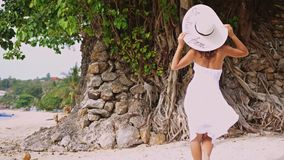 Young brunette woman with long hair in white drees and hat walking on a tropical beach. slow motion. 3840x2160 stock footage