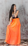 Young brunette woman in long orange skirt Stock Photo