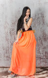 Young brunette woman in long orange skirt Stock Images