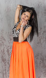 Young brunette woman in long orange skirt Royalty Free Stock Images
