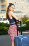 Young brunette woman with luggage. Portrait of beautiful young traveler woman with suitcase Stock Image