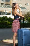 Young brunette woman with luggage. Portrait of beautiful young traveler woman with suitcase Stock Photo