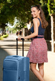 Young brunette woman with luggage. Royalty Free Stock Photos