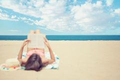 Young brunette woman lying on the beach reading a book stock photos