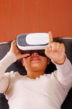 Young brunette woman lying down wearing virtual reality goggles experiencing future technology, interacting and smiling. While playing, vr concept Stock Images