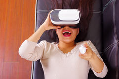 Young brunette woman lying down wearing virtual reality goggles experiencing future technology, interacting and smiling. While playing, vr concept Royalty Free Stock Images