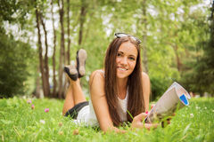 A young brunette woman lying on the grass outdoors Royalty Free Stock Image