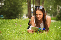 A young brunette woman lying on the grass outdoors with a magazi Stock Images