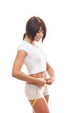 A young brunette woman measuring her waist Royalty Free Stock Photos
