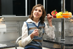 A young brunette woman in a modern kitchen Stock Image