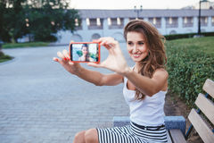 Young brunette woman in park doing selfie stock photos
