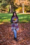 A young brunette woman in a park surrounded by fall leaves. stock photo