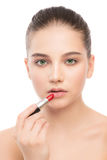 Young brunette woman with perfect clean face applying lipstick. Isolated on a white. Stock Images
