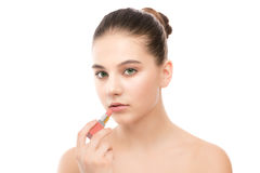 Young brunette woman with perfect clean face applying lipstick. Isolated on a white. Royalty Free Stock Image