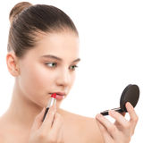 Young brunette woman with perfect clean face applying lipstick using mirror. Isolated on a white. Royalty Free Stock Photography