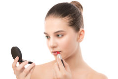 Young brunette woman with perfect clean face applying lipstick using mirror. Isolated on a white. Stock Images