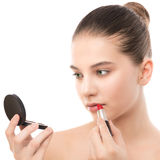 Young brunette woman with perfect clean face applying lipstick using mirror. Isolated on a white. Stock Photos