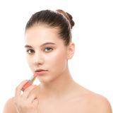 Young brunette woman with perfect clean face applying lipstick.  on a white. Royalty Free Stock Images
