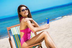 A young brunette woman in a pink swimsuit on the beach Royalty Free Stock Photography