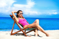 A young brunette woman in a pink swimsuit on the beach Royalty Free Stock Photos