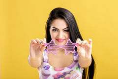 Young brunette woman in pink tank top on yellow background. funny girl with pink sunglasses. focus on glasses Royalty Free Stock Photo