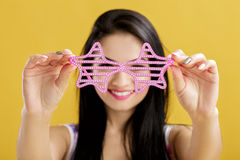 Young brunette woman in pink tank top on yellow background. funny girl with pink sunglasses. focus on glasses Stock Image