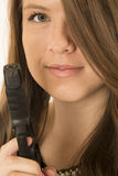 Young brunette woman with a pistol and her hair over one eye Royalty Free Stock Photography