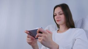 Young brunette woman is playing game on mobile phone. stock footage