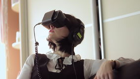 Young brunette woman playing game using VR-helmet for smart phones. Augmented reality device allows to deep into virtual stock video