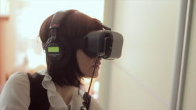 Young brunette woman playing game using VR-helmet for smart phones. Augmented reality device allows to deep into virtual stock footage
