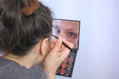 Young brunette woman plucks her eyebrows with tweezers in front of the mirror at home. stock photos