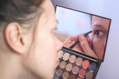Young brunette woman plucks her eyebrows with tweezers in front of the mirror at home. royalty free stock photos