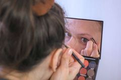 Young brunette woman plucks her eyebrows with tweezers in front of the mirror at home. stock images