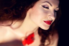 Young brunette woman and poppies. Young sensible woman with red poppies, red lipstick and radiant skin stock photo