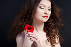 Young brunette woman and poppies. Young sensible woman with red poppies, red lipstick and radiant skin royalty free stock photography