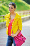Young brunette woman portrait in colorful clothes in summer park Royalty Free Stock Photo