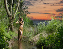 A young brunette woman posing in a green forest Royalty Free Stock Photo