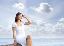 A young brunette woman posing near the sea Royalty Free Stock Images