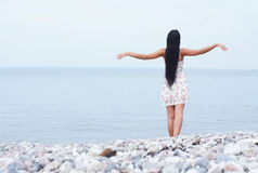 A young brunette woman posing near the sea Stock Photo