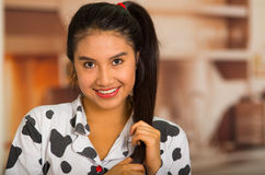 Young brunette woman posing in pyjamas, holding hair and smiling to camera Stock Photography
