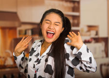 Young brunette woman posing in pyjamas, interacting with camera by stretching and yawning Royalty Free Stock Image