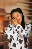 Young brunette woman posing in pyjamas, interacting sleeping with eyes closed using hands and smiling to camera Stock Photo