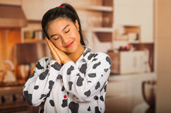 Young brunette woman posing in pyjamas, interacting sleeping with eyes closed using hands and smiling to camera Royalty Free Stock Image
