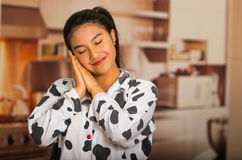 Young brunette woman posing in pyjamas, interacting sleeping with eyes closed using hands and smiling to camera Stock Photography