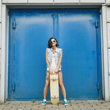 Young brunette woman posing with skateboard Stock Photography