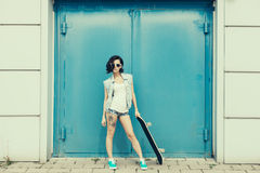 Young brunette woman posing with skateboard Royalty Free Stock Photo