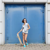 Young brunette woman posing with skateboard Stock Images