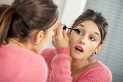 Young brunette woman putting makeup in the mirror stock images