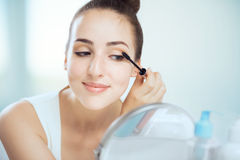 A young brunette woman putting on mascara Royalty Free Stock Image